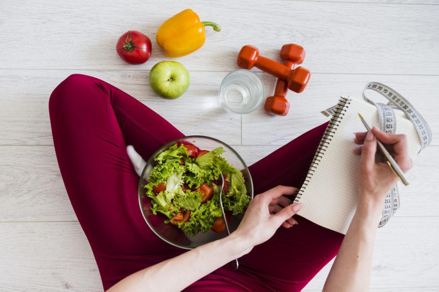 Vista de cima de uma mulher sentada no chão anotando algo em um caderno que tem uma fita métrica em cima. Ela tem uma vasilha de salada no colo e pesos de academia, frutas, legumes e uma copo de água perto.