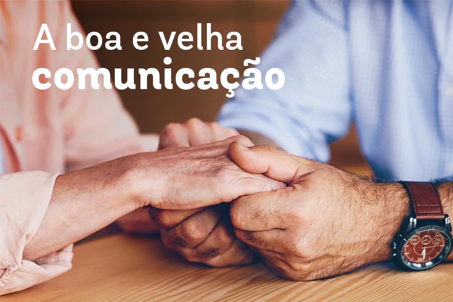 Close de duas pessoas, um homem em uma mulher, segurando as mãos um do outro com os dizeres a boa e velha comunicação