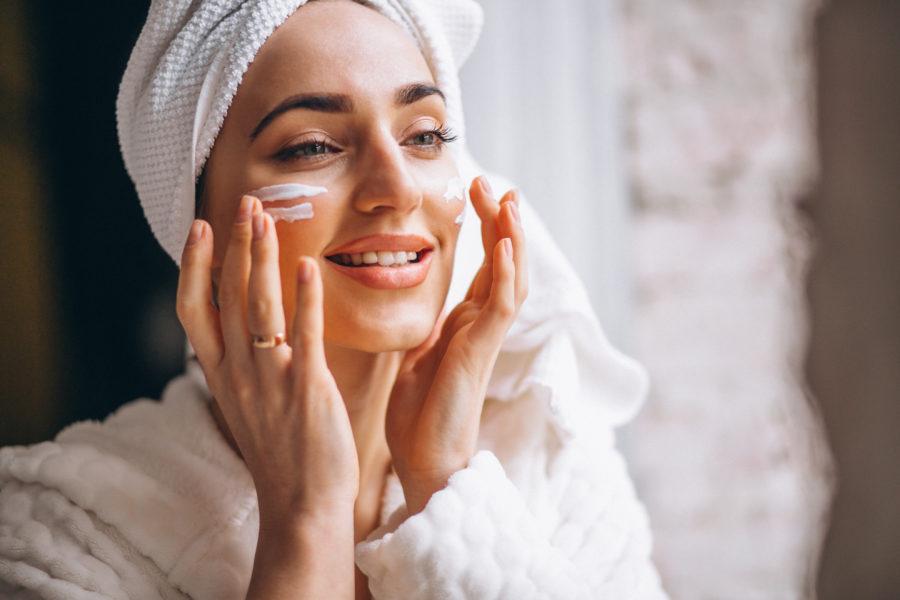 Mulher passando creme à base de ácido hialurônico no rosto