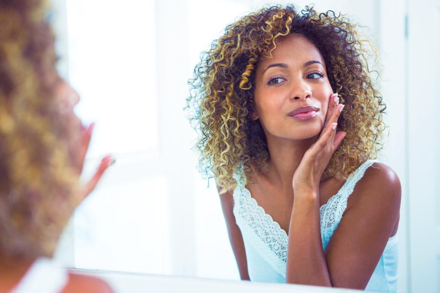Mulher negra negra alisando a pele do rosto na frente do espelho