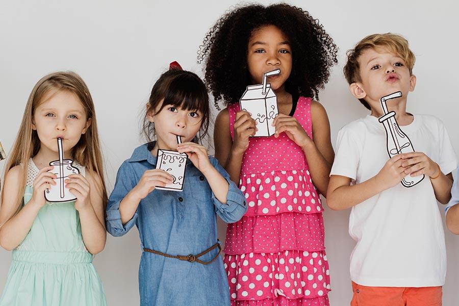 Crianças segurando papel com desenhos simulando que estão bebendo bebidas com adição de adoçante