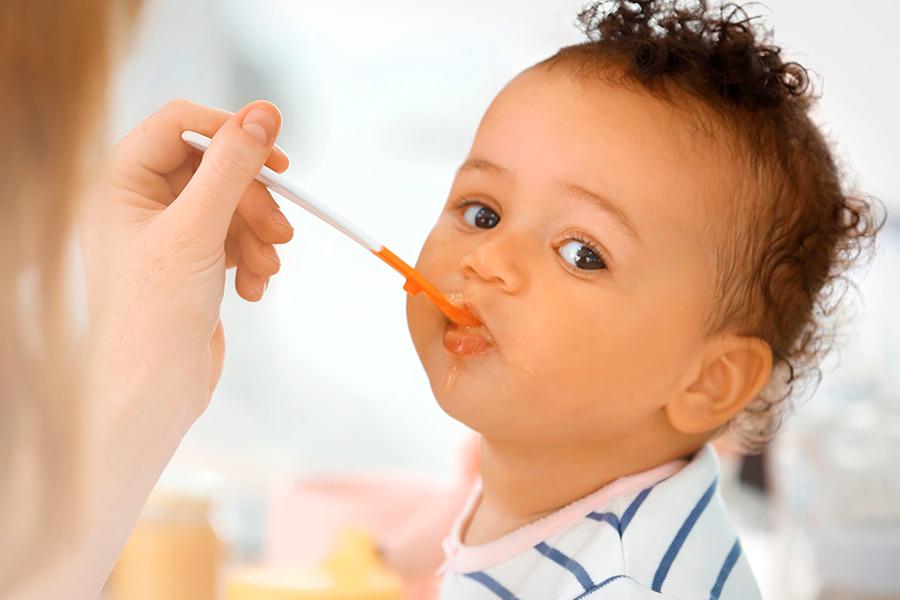 Bebê sendo alimentado na boca por uma mulher com uso de uma colher branca e laranja