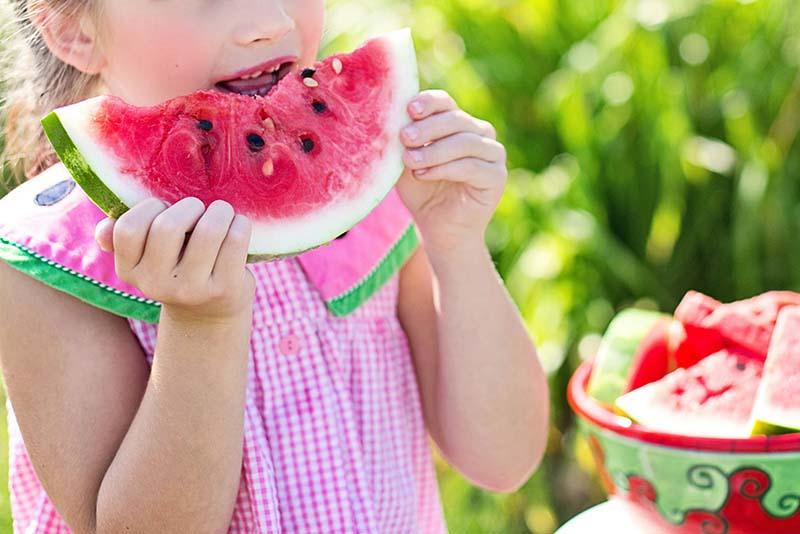 Criança menina comendo uma melancia