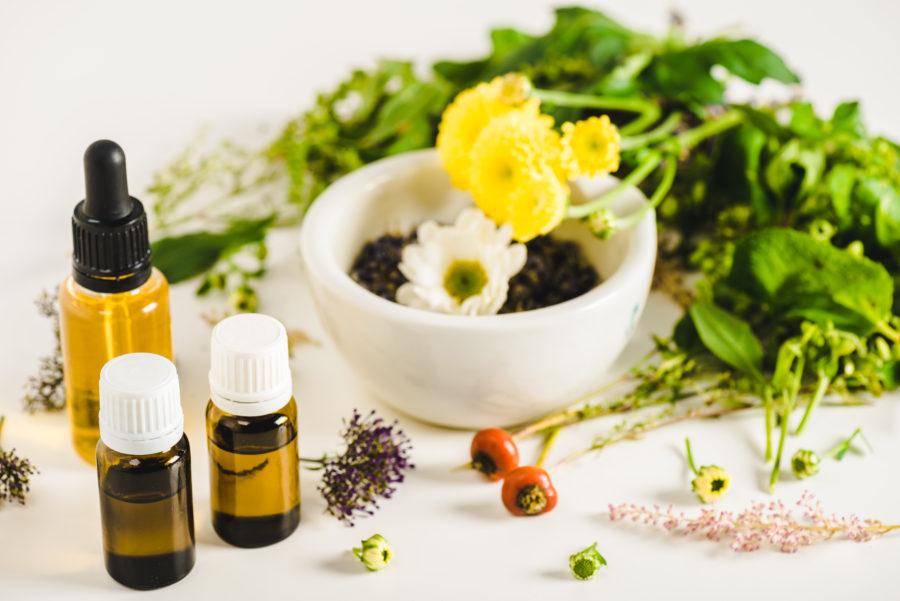 Frascos de óleos essenciais e tigela com flores e plantas usadas na aromaterapia