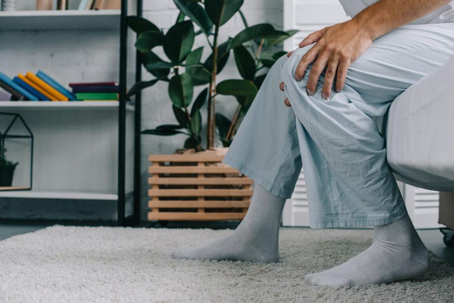 Homem com as mãos no joelho indicando dores, um sinal de que ele precisará de uma artroscopia