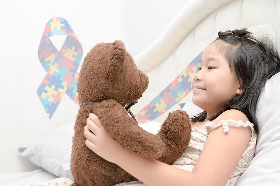 Menina autista segurando seu ursinho de pelúcia e olhando fixamente para ele. Fita símbolo do autismo ao fundo