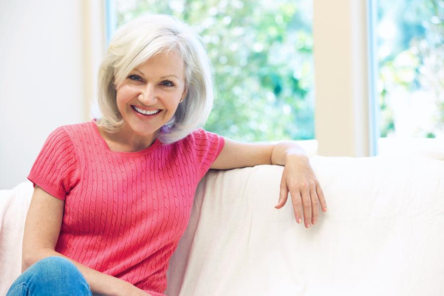 Mulher mais velha sorridente sentada no sofá