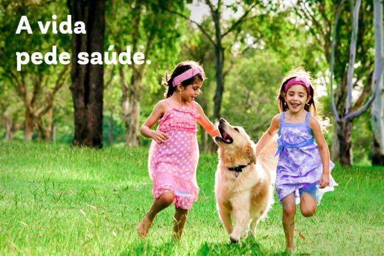 Duas meninas correndo na grama com um cachorro e os dizeres a vida pede saúde