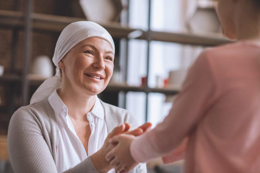 Mulher mais velha com câncer de mama segurando a mão de uma criança