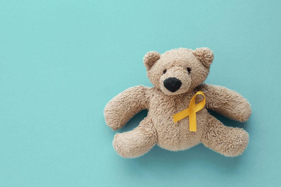 Urso de pelúcia com fita amarela sob um fundo azul piscina representando o o combate ao câncer infantil