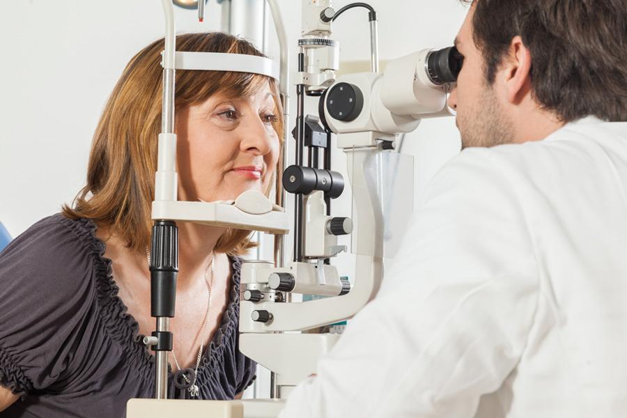 Oftalmologista homem examinado catarata nos olhos de uma senhora