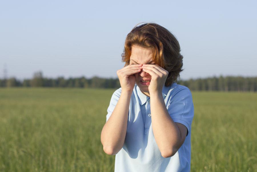 Mulher ao ar livre coçando os olhos. Uma ação que pode causar ceratocone