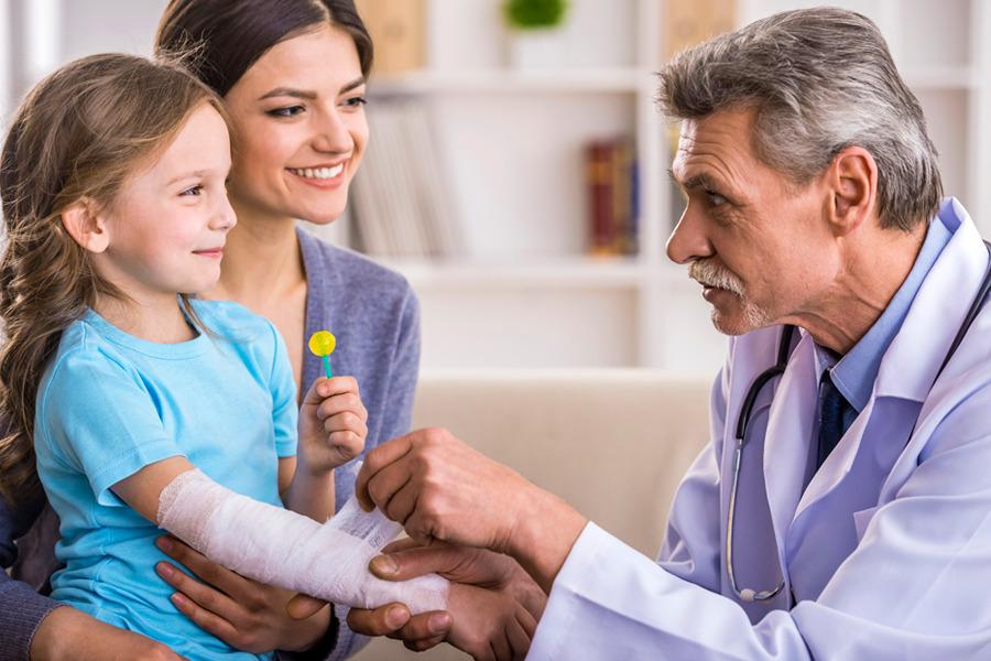 médico enfaixando braço de uma menina para proteger as queimaduras