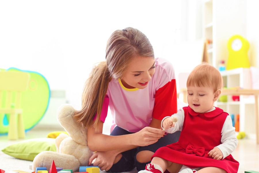 babá brincando com criança em uma sala com alguns brinquedos