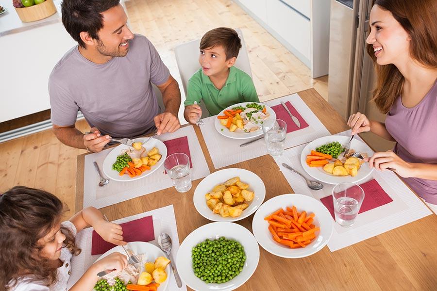 Cena de uma família feliz composta de pai e mãe e um casa de crianças comento uma refeição saudável à mesa. Essa cena representa um comportamento alimentar