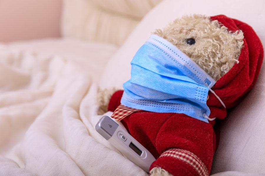 Representando a coronavírus em crianças, ursinho de pelúcia na cama em baixo das cobertas com uma máscara e um termômetro
