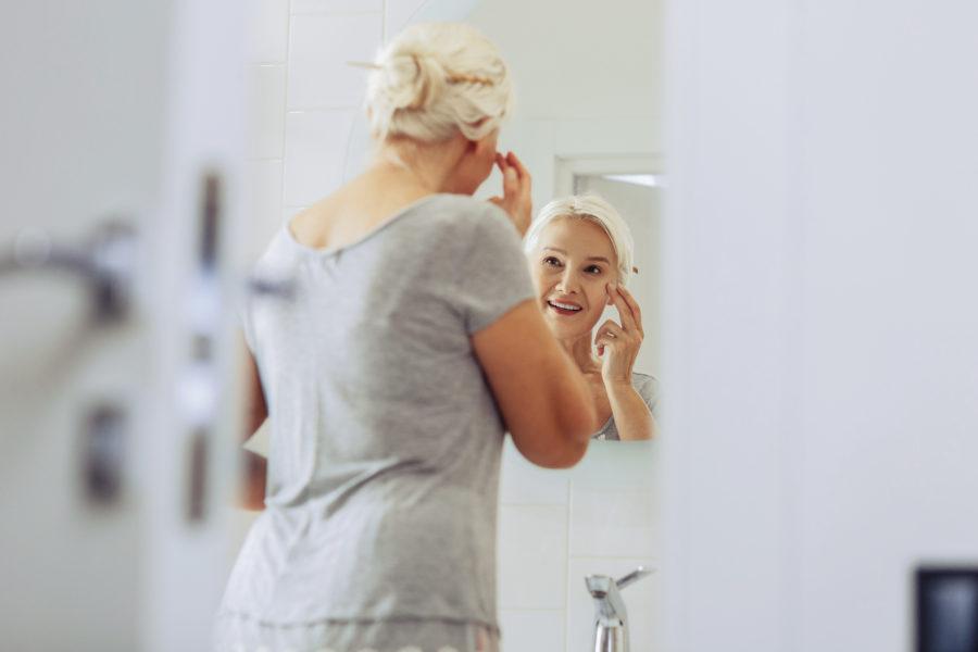 Mulher mais velha passando cosmético anti-idade no rosto enquanto se olha no espelho do banheiro