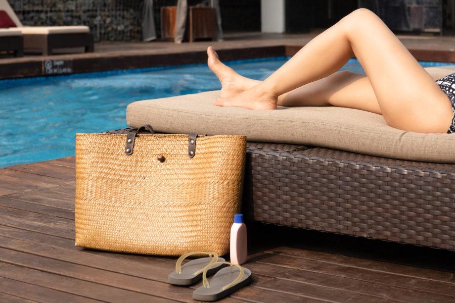 É verão. Mulher deitada em uma cadeira na frente da piscina. Ao lado dela uma bolsa, um frasco de protetor solar e um par de chinelos, aliados no cuidados com a pele no verão para evitar doenças de pele