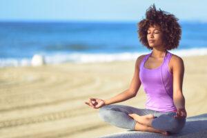Mulher sentada ao ar livre em posição de meditação
