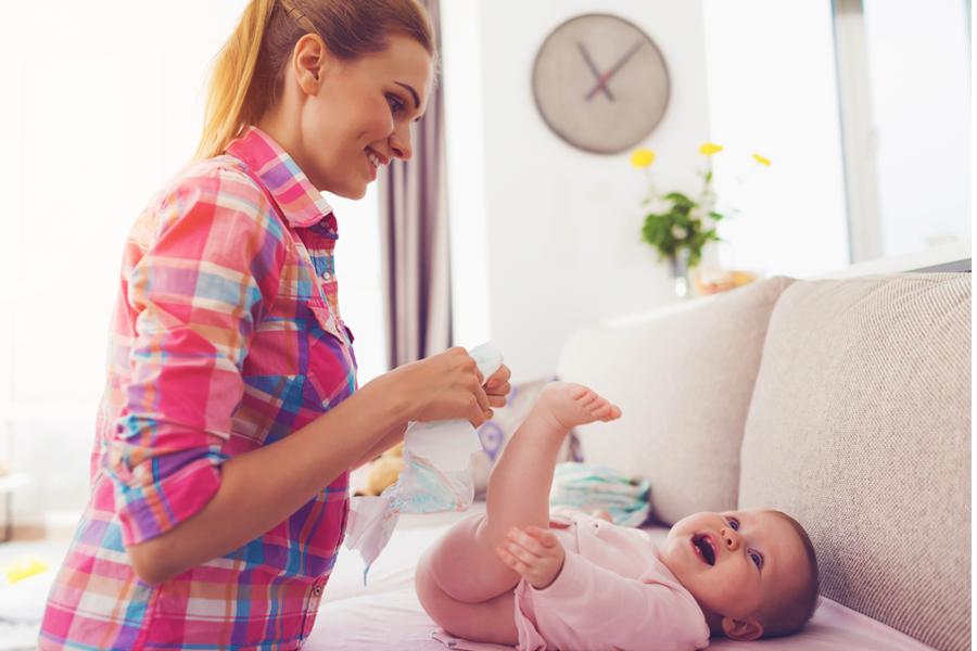 Mãe trocando, em um sofá, a fralda de seu bebê