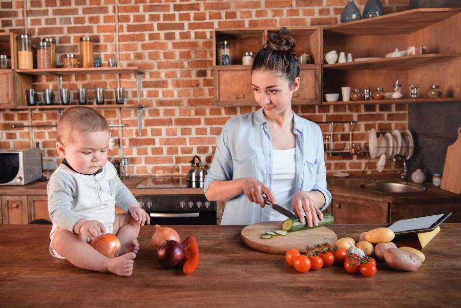 Mão na cozinha com seu filho. Mulher está preparando comida enquanto olha seu filho que está brincando com cebolas. A dieta da mãe é importante para a amamentação