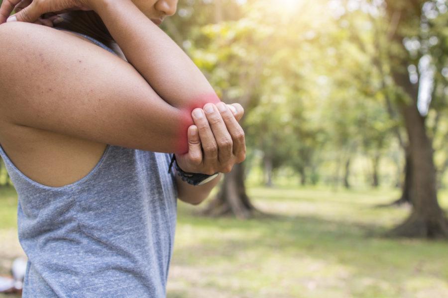Close de homem ao ar livre segurando o cotovelo sinalizado de vermelho por estar com uma dor proveniente da síndrome do túnel cubital