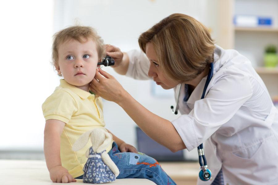 Pediatra mulher examinando o ouvido de uma criança que está com dor de ouvido