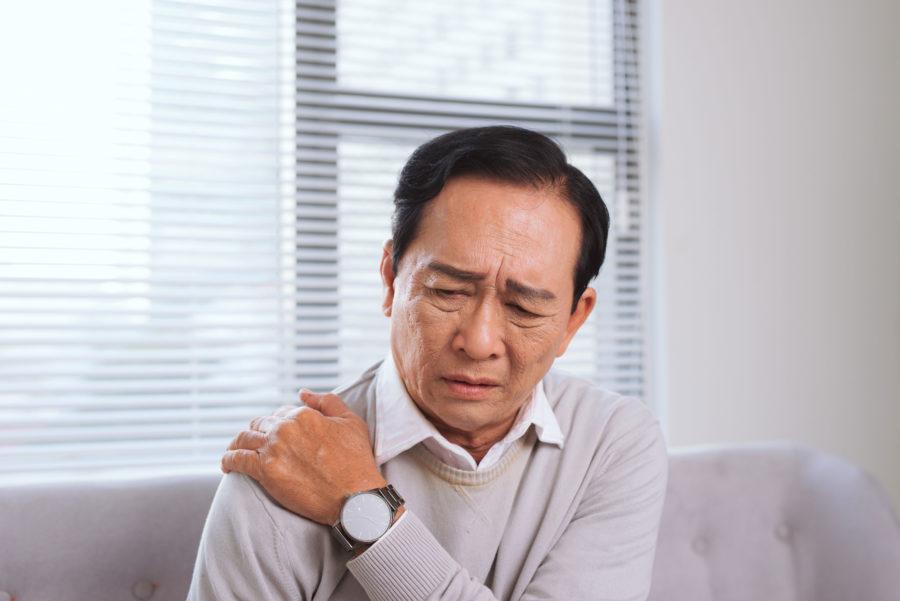 Homem asiático mais velho com a mão no ombro e o rosto indicando dor proveniente de alguma lesão