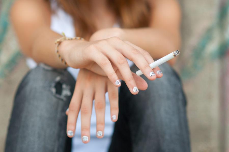 Close de mão de mulher segurando um cigarro