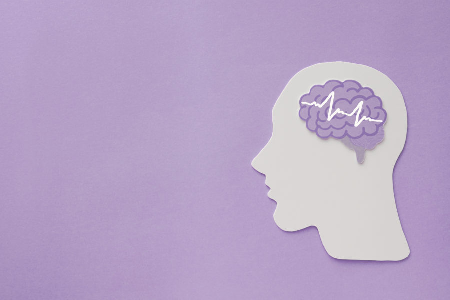 Rosto de papel e um cérebro em um fundo roxo para representar a epilepsia