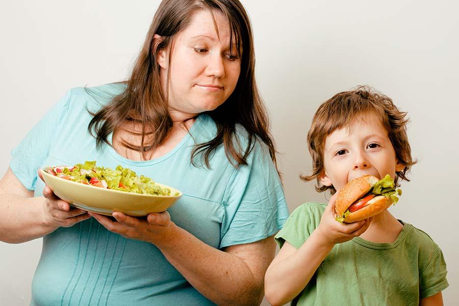Mãe com prato de salada nas mãos olhando para seu filho que está comendo um hambúrguer