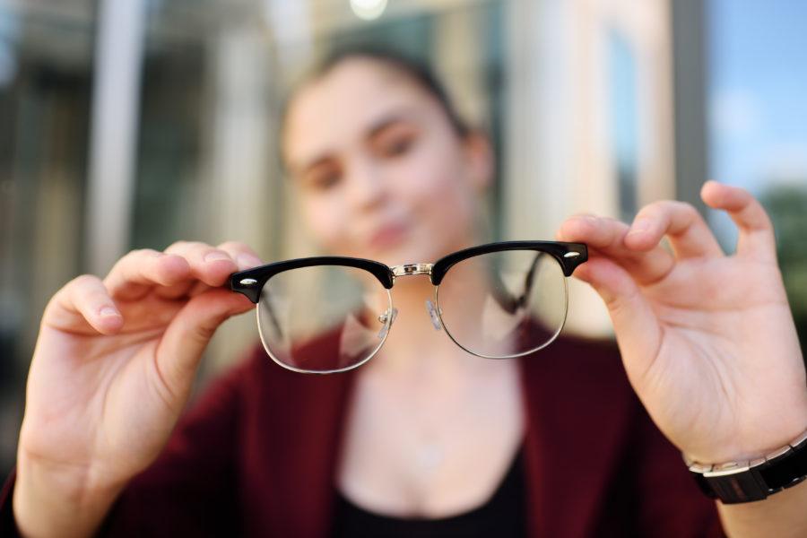 Garota segurando um óculos em primeiro plano focado. Ao fundo, ela e o fundo estão desfocados para representar erros refrativos