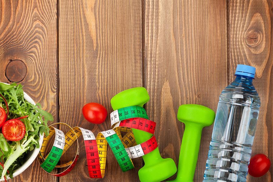 salada, fita métrica, alter de academia e uma garrafa com água sob um fundo de madeira