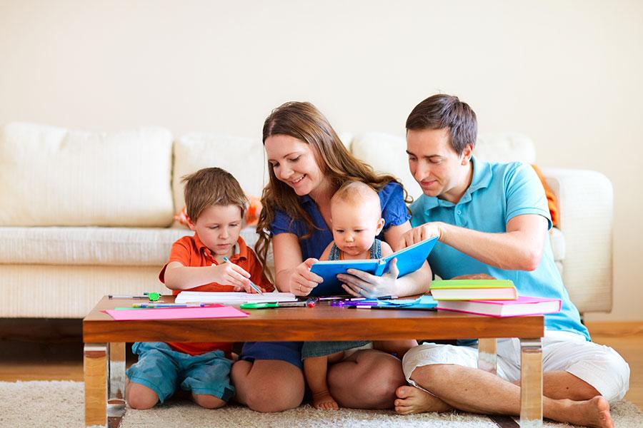 Pais sentados no chão da sala ensinando seus dois filhos a ler e a desenhar mostrando um dos estilos parentais