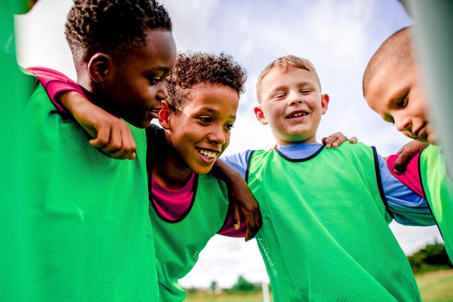 garotos com coletes de futebol se abraçando e sorrindo