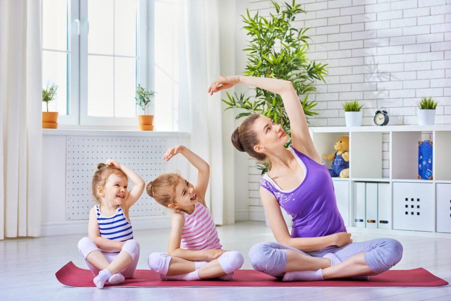 Crianças pequenas praticando exercício físico na infância junto de sua mãe