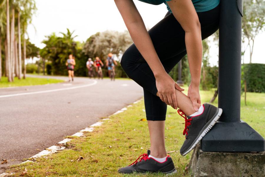 Ao ar livre, mulher corredora segurando o tornozelo da perna por ter sofrido uma fratura por estresse