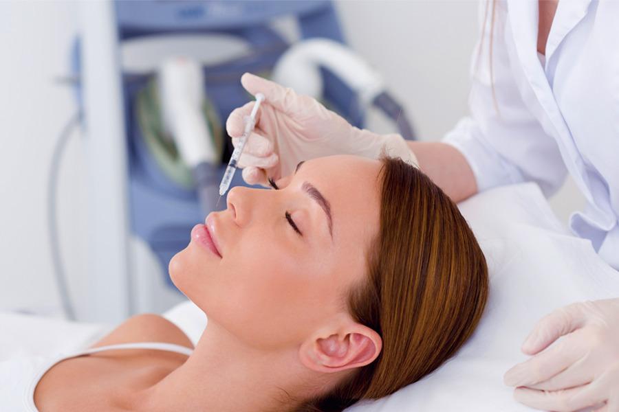 Close de rosto de uma mulher deitada em uma cama com uma médica aplicando uma injeção em seu rosto para realizar a harmonização facial