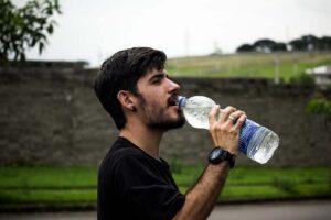Homem ao ar livre bebendo água de uma garrafa