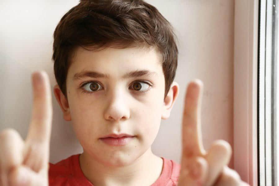 Menino que tem estrabismo olhando fixamente para seus dois dedos indicadores