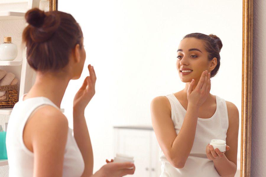 Mulher com melasma em frente ao espelho passando creme no rosto