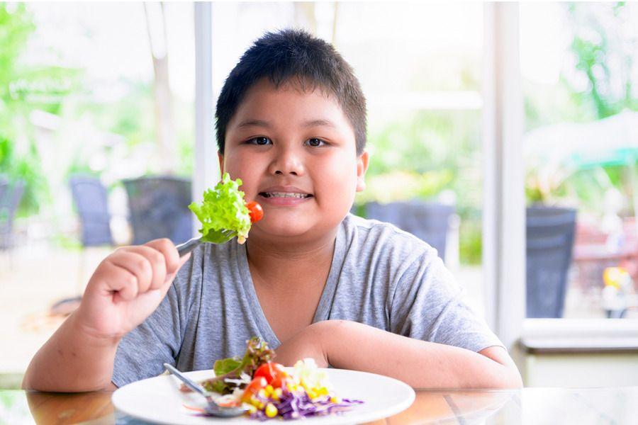 Garoto obeso comendo um prato de salada