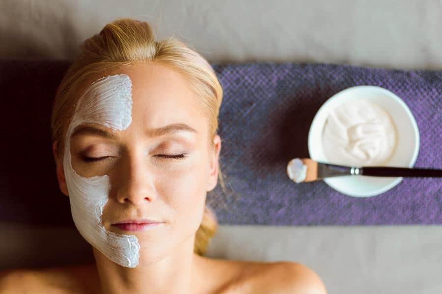 Vista de cima de mulher com creme aplicado em metade do rosto dela. Ao lado, a tigela com o creme e o pincel. Ela está passando por um sessão de limpeza de pele.