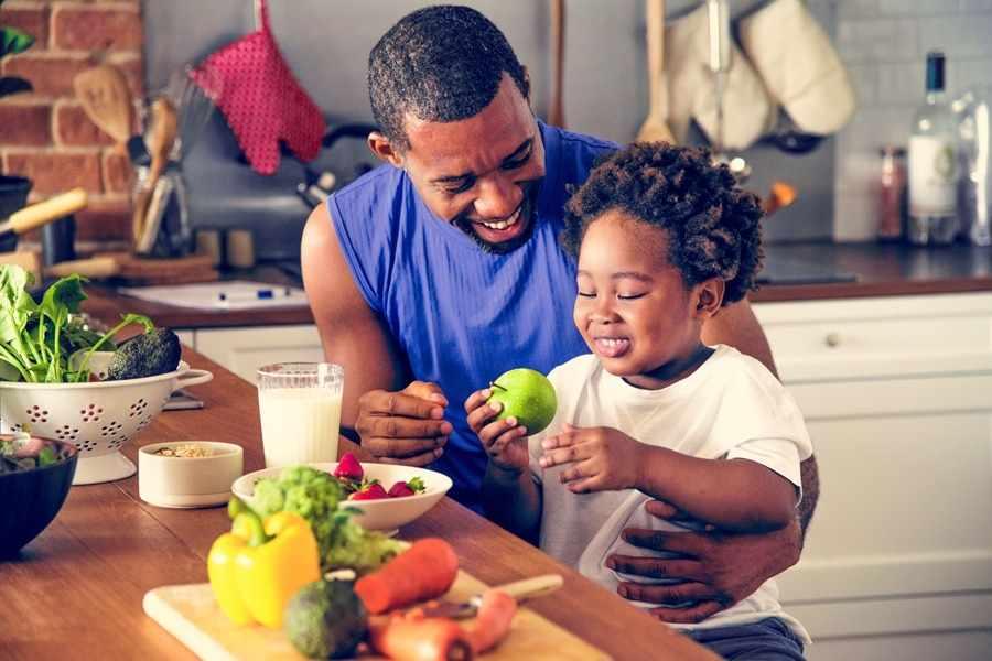 Pai e filha sorridentes preparando uma alimentação infantil saudável na cozinha.
