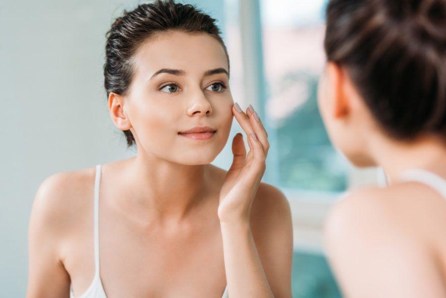 Mulher se olhando no espelho com o nariz bonito depois de ter feito uma rinomodelação
