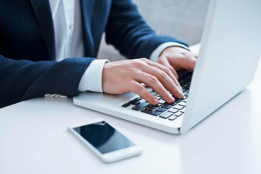 Detalhe de um homem de terno digitando em um notebook simbolizando os efeitos do uso constante do computador para a visão