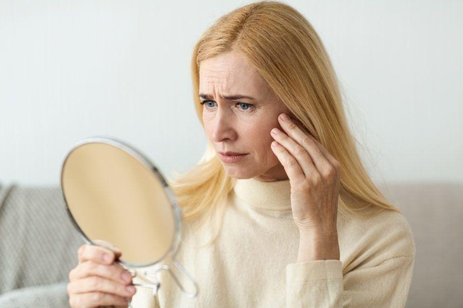 Mulher de meia idade com mão no rosto e cara de preocupação se olhando no espelho. Ela aparenta ter pele flácida. Uma solução são os bioestimuladores