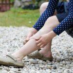 Detalhe de moça com varizes passando bandagem na perna