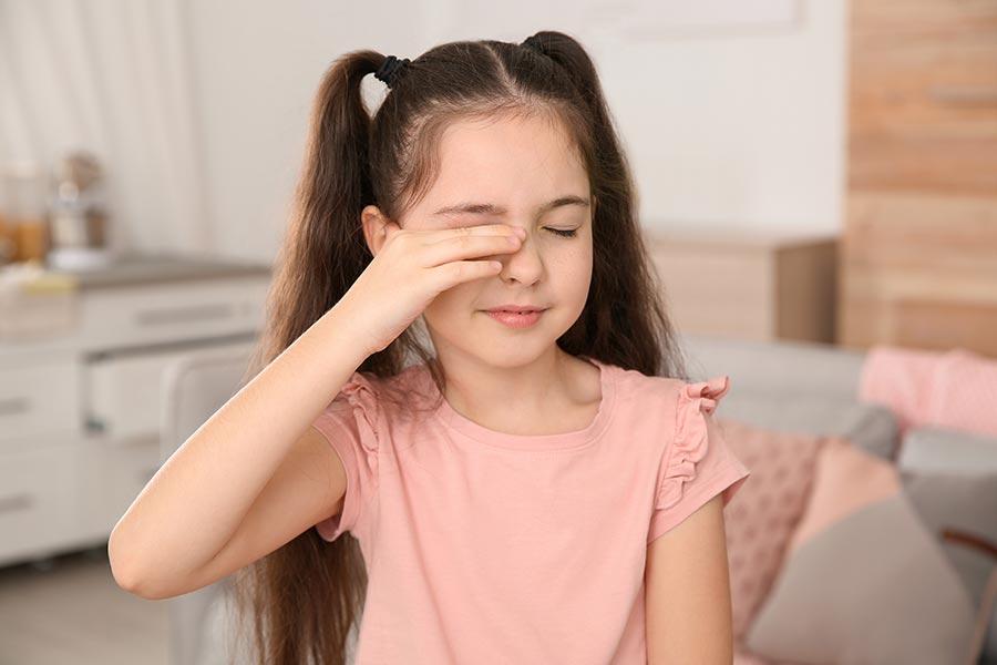 Menina coçando o olho devido a uma alergia