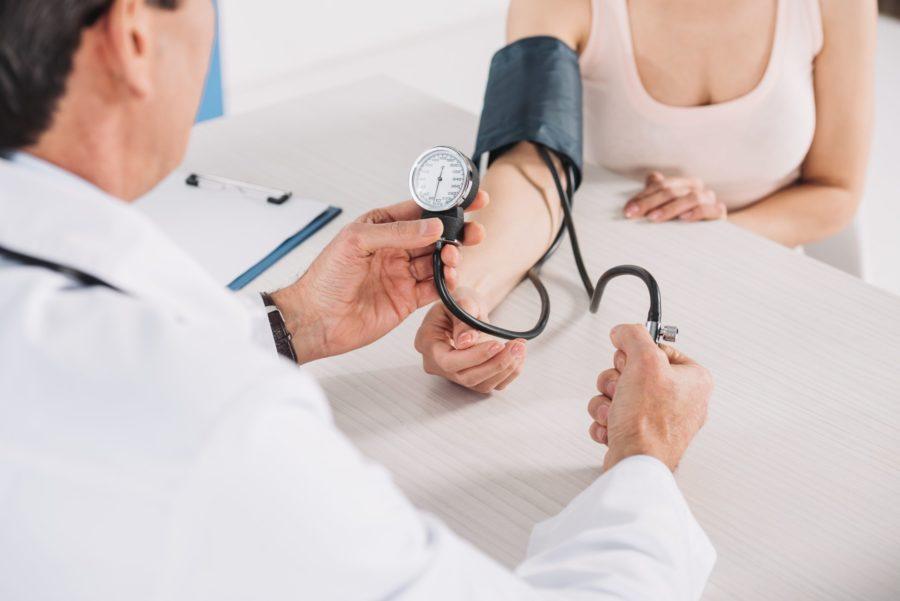Detalhe de médico aferindo a pressão de uma paciente para saber se ela tem hipertensão arterial